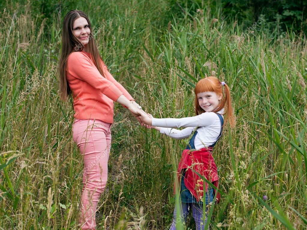 Glückliche Mutter und Tochter Hand in Hand und auf der Suche in den ...