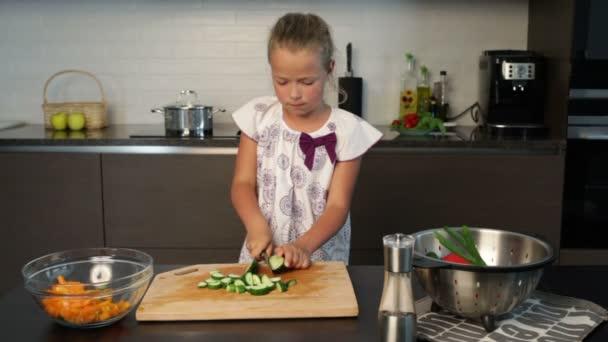Malá holčička připravuje salát v kuchyni