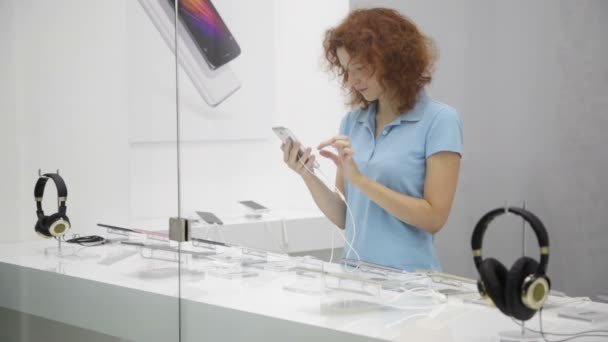 Woman choosing smartphone in store