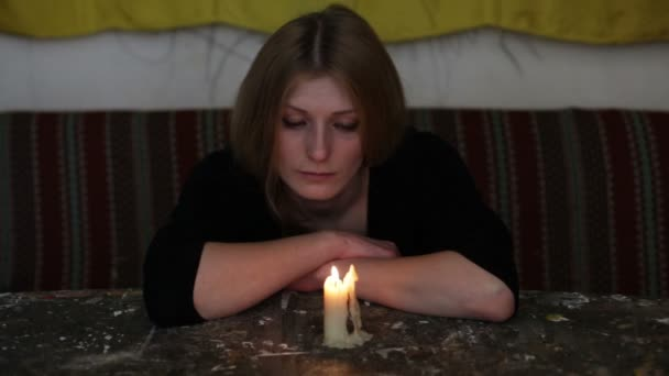 Young sad woman sitting with a candle