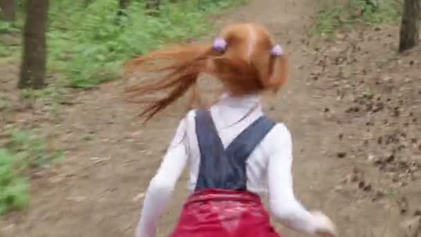 Ginger little girl running through the woods