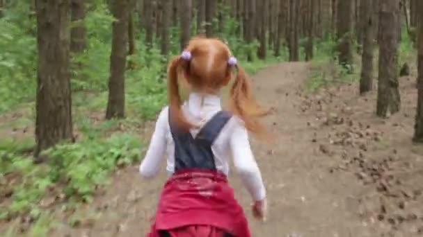 Ginger little girl running through the woods