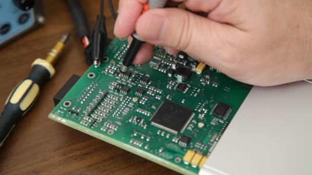 Engineers hand holding the oscilloscope probe