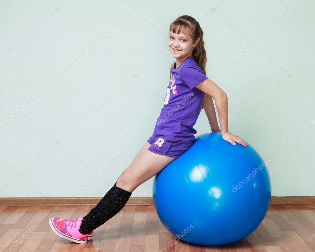 Petite Fille En Costume De Sport Violet Est Assis Sur Un Bleu Ba D