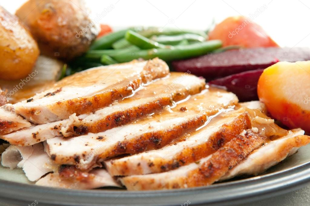Sliced turkey with roasted potatoes, sugar beets, yams and green beans