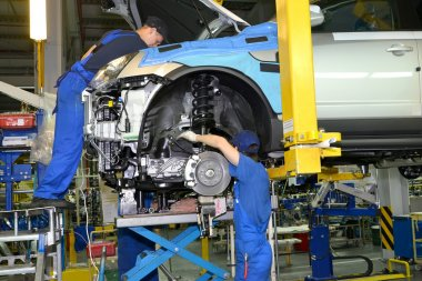 Workers install the engine on the car. Assembly conveyor of auto
