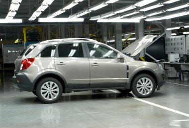 The new car with an open cowl costs in assembly shop. Automobile