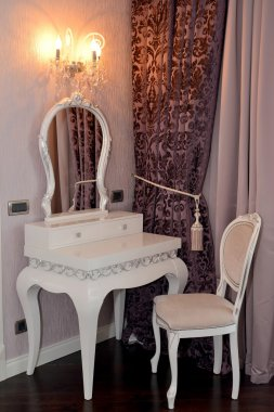 White dressing table and chair in a living room. Modern classics