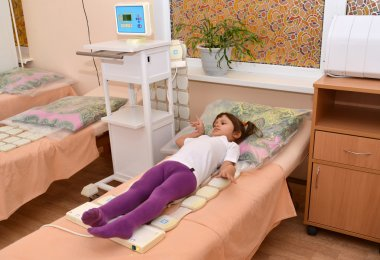 The little girl receives procedure of a magnetotherapy. Physioth