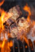 Fotografie pork steak on bbq grill with flame