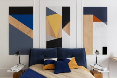 Bedroom interior in modern style with a large bed and paintings