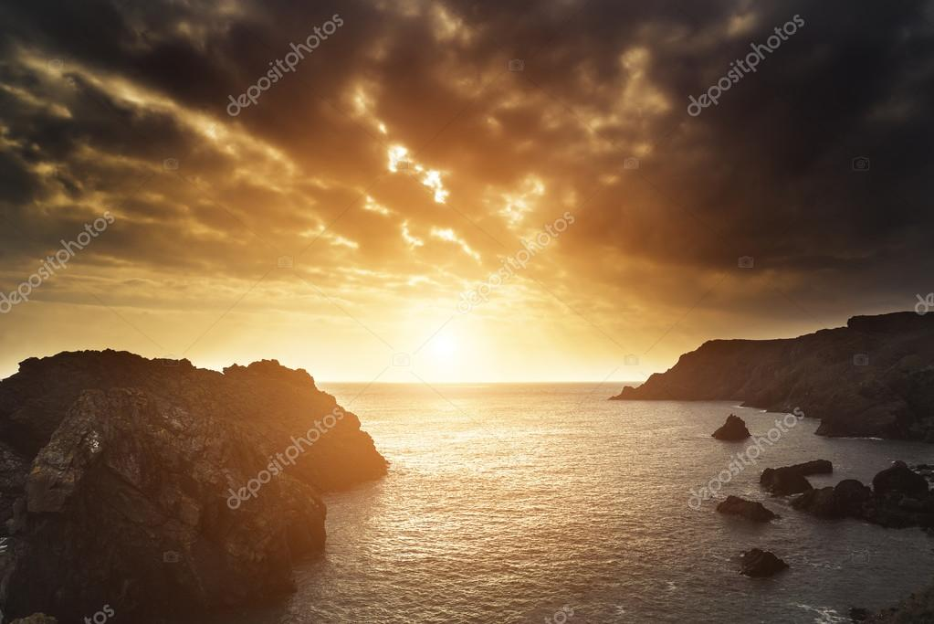 Beautiful sunset landscape over rocky cove looking out to sea