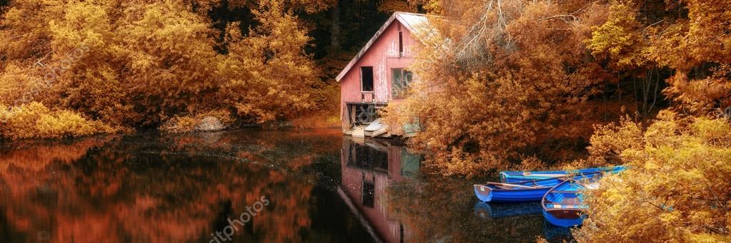 Panorama landscape stunning vibrant Autumn scene boat lake and b