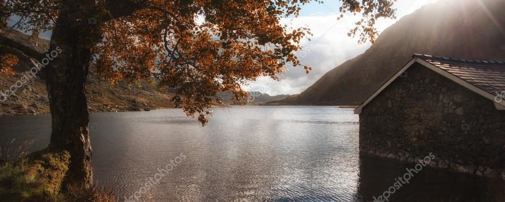 Panorama landscape fishing hut on mountain lake in Autumn