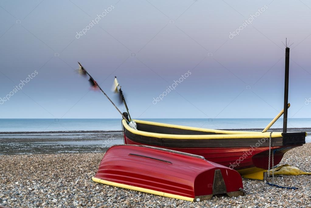 Landscape image of small fishing boats on beach at sunrise in Sp