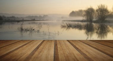 Landscape of lake in mist with sun glow at sunrise with wooden p