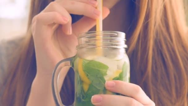Girl drinking lemonade in glass jar.
