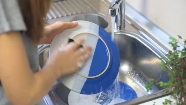 Uzavřete ruce ženy, mytí nádobí v kuchyni