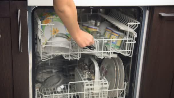 myčka nádobí. šťastná mladá žena v kuchyni dělat domácí práce.