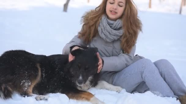 Beautiful girl playing with a dog in the snow