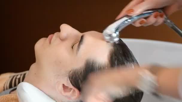 Muž kadeřnictví praní mužské vlasy v holičství