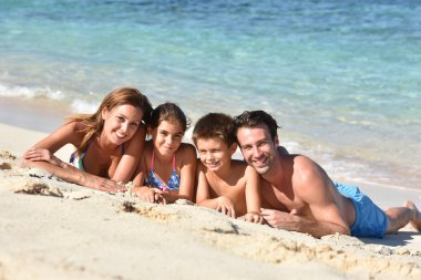 Family laying on a sandy beach