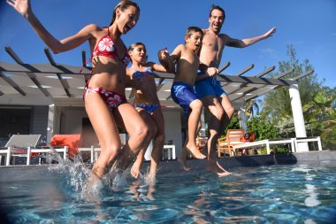Family jumping into l swimming pool