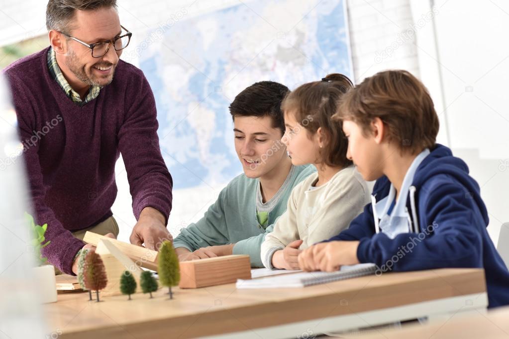 Преподаватель в классе естественных наук с учениками ...