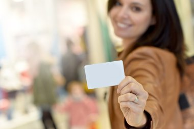 woman holding card in shopping mall
