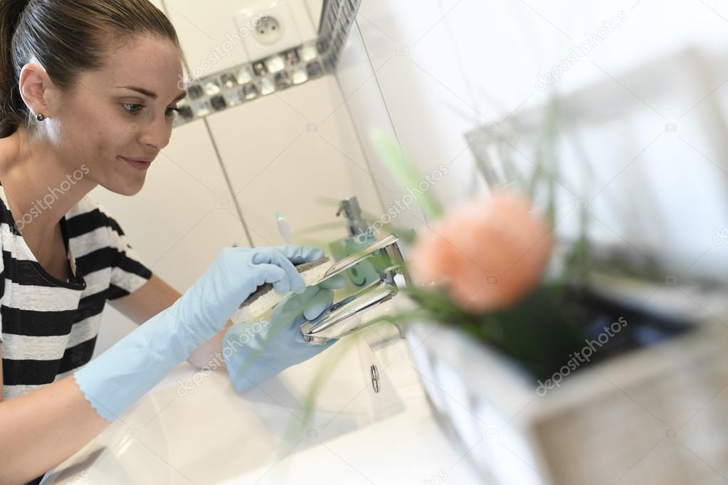 Frau Reinigung Badezimmer Wasserhahn — Stockfoto © Goodluz #119993426