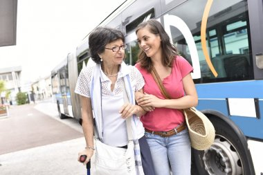 woman with carer getting off the bus