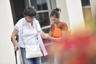 carer helping  woman getting down