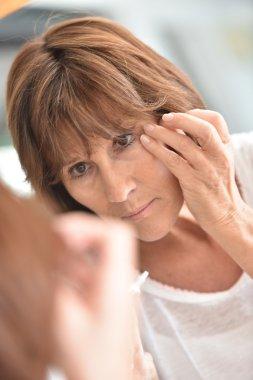 woman applying eye concealer