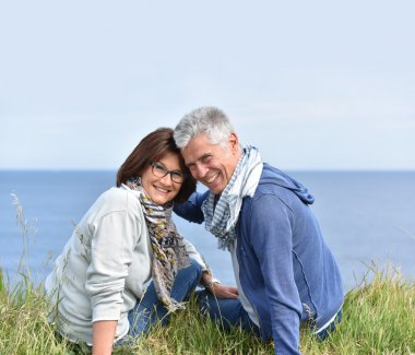 Mature couple on rambling day sitting by cliff stock vector