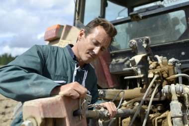 Farmer working on tractor