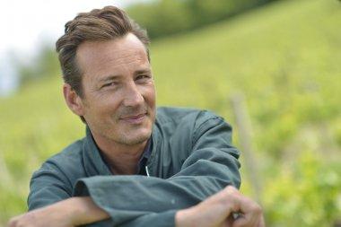 Smiling vinegrower standing in vineyard