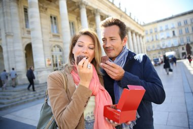 Couple in Bordeaux eating cakes