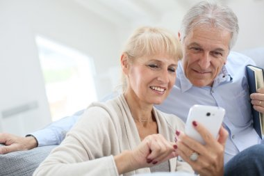 Couple at home using smartphone