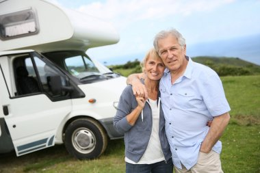 Couple standing in front of camping car