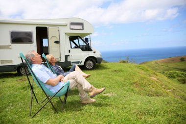 Couple relaxing in camping folding chairs