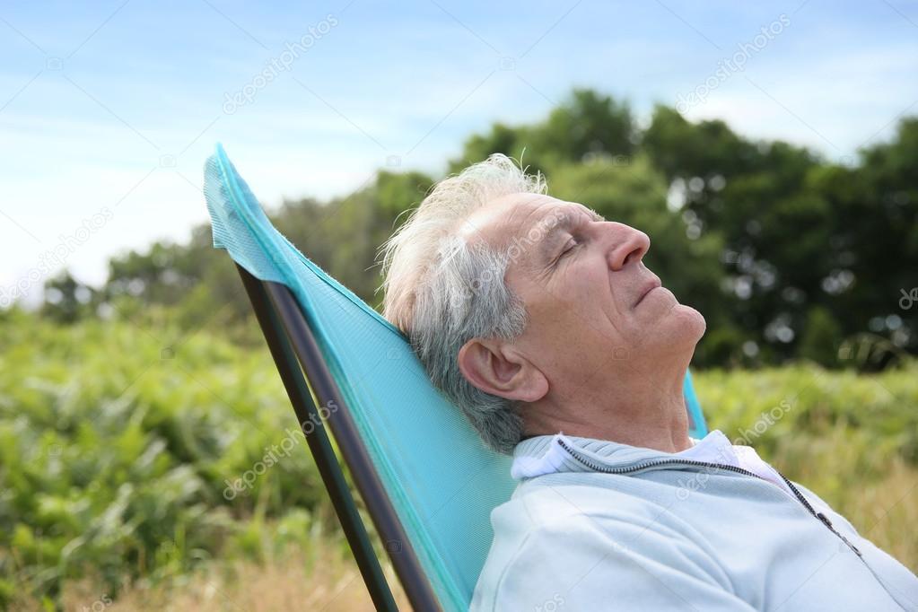 Senior man relaxing in camping chair