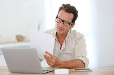 Adam evde dizüstü bilgisayarla çalışıyor.