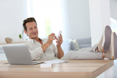 Relaxed man using smartphone