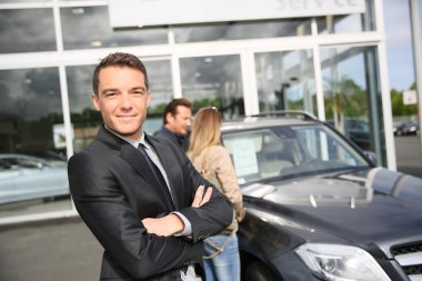 Smiling car dealer standing by vehicle