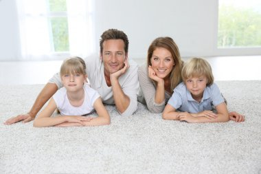 Family laying on carpet at home