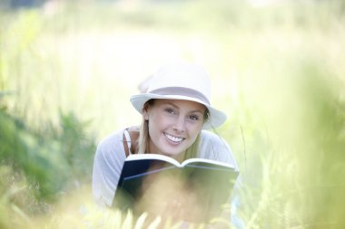 Smiling woman laying in grass and reading book stock vector