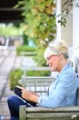 Fotografie Starší žena čte knihu na lavičce