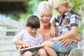 Grandmother with kids playing on tablet