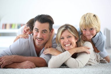 Happy family laying on carpet