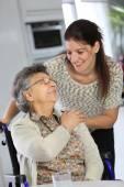 Žena na vozíku s domácí pečovatel